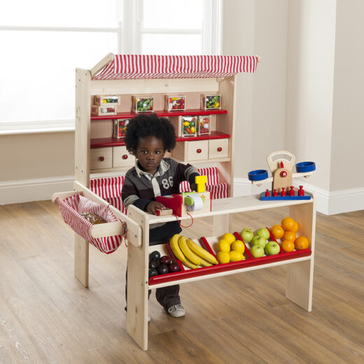 wooden market stall toy with basket and shelves at the back