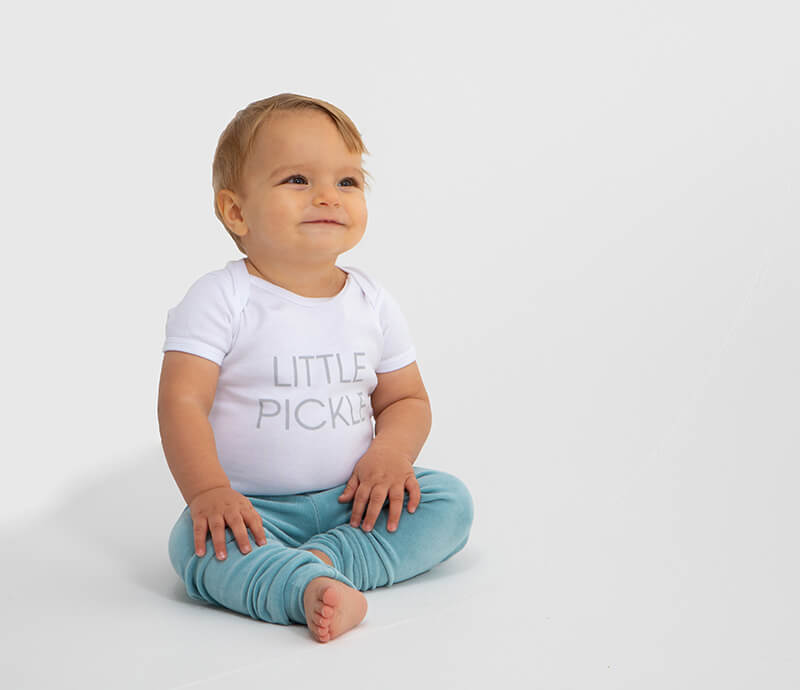 little boy sitting wearing a white bodysuit with little pickle print in grey and a pair of velour legging