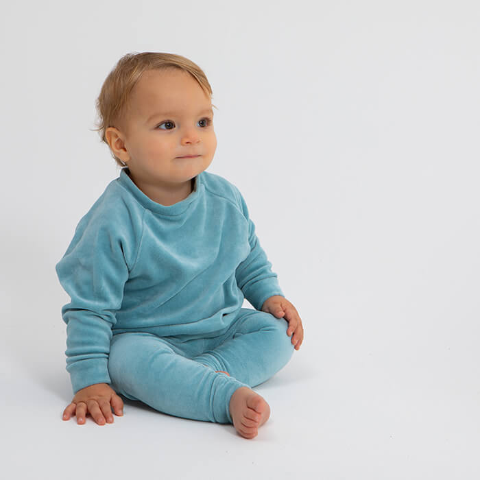 toddler sitting wearing velour top and leggins