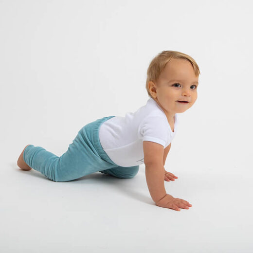 little boy wearing a white bodysuit with velour legging in dark mint colour