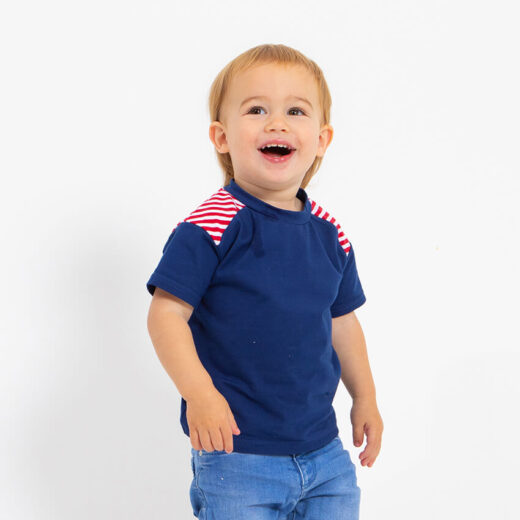 boy wearing dark blue tshirt with stripe detail on the shoulder red and white