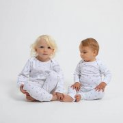 little girl and little boy sitting down both wearing white pyjama with the word pickle printed all over in grey