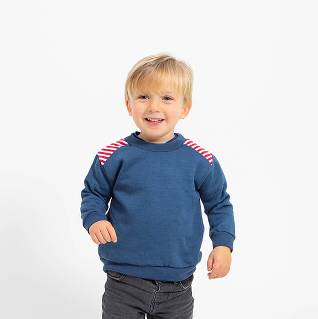 boy wearing dark blue sweatshirt with detail on the shoulder of red and white stripes