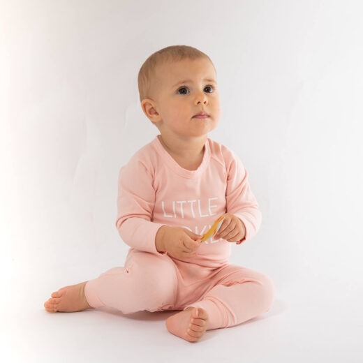 baby girl wearing pink romper with little pickle printed in white