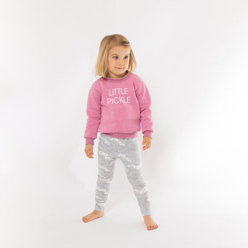 girl wearing pink sweatshirt with little pickle printed in white